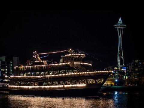 Bateau illuminé passant devant la Space Needle lors du festival Argosy Christmas Ships & Bonfires